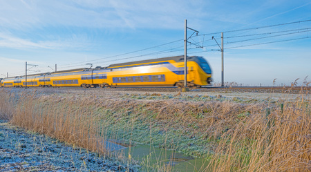 Electric train in a sunny frozen landscape Imagens