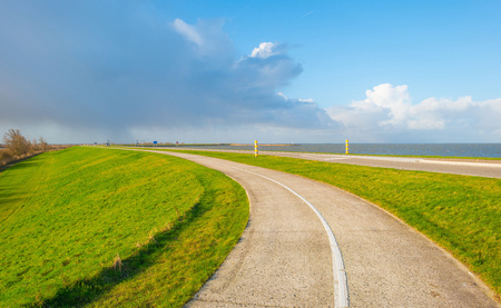 Road on a dike along a lake Stock Photo