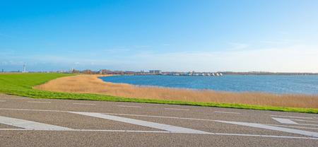 lelystad: Road on a dike along a lake Stock Photo