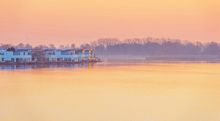 lelystad: Shore of a lake in winter at sunrise