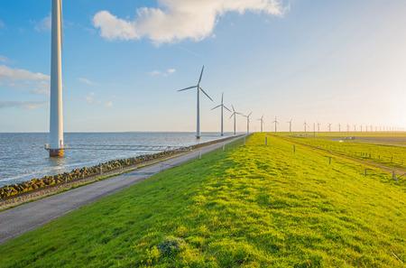 dyke: Wind turbines along a dyke in spring Stock Photo