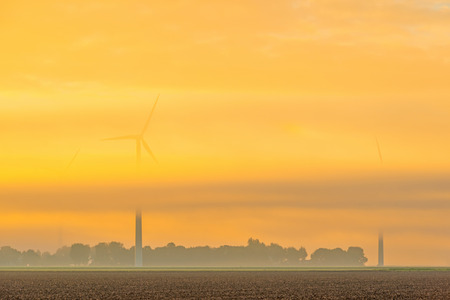 Wind turbine in a foggy field at sunrise Stock Photo