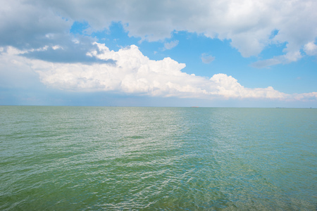 markermeer: Barge sailing on the horizon of a lake below a blue cloudy sky