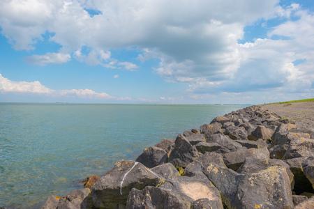 Dikke basalt stenen langs een meer in het voorjaar