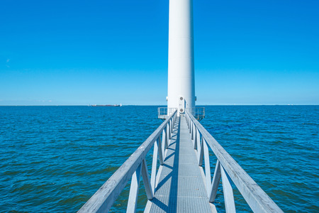 Footbridge towards a wind turbine along a coastline Stock Photo