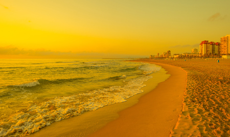 valencia orange: Sunrise in orange over a beach in summer Stock Photo