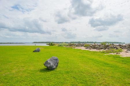 Kustlijn van basalt stenen langs een meer in zonlicht in de zomer