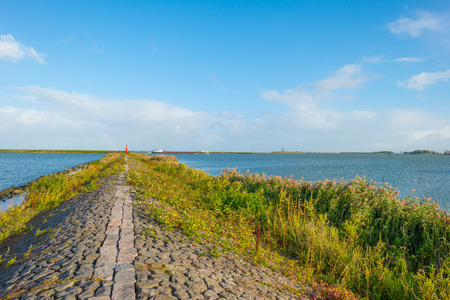 markermeer: Boat sailing along a dike in a lake in summer
