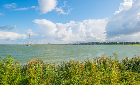 markermeer: Boat sailing along a dike in a stormy lake in summer