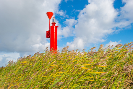 markermeer: Red beacon on a stormy dike in sunlight in summer