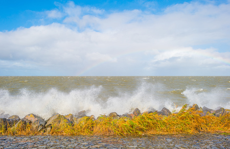shorelines: Dike along a stormy lake in sunlight in autumn