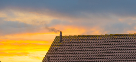 Smoking chimney on a roof at sunrise in autumn