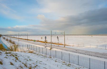 Railway through a snowy field in sunlight in winter Stock Photo