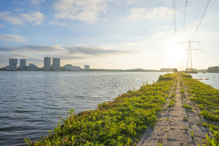 Skyline of a city along the shore of a lake at sunrise in spring Stock Photo