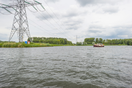 Powerline over the shore of a lake in spring