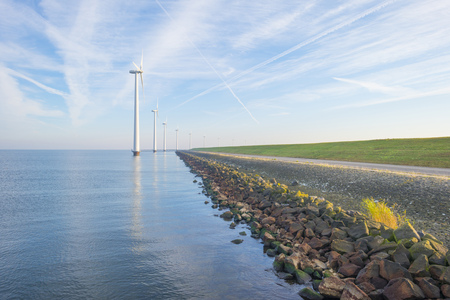 Wind turbines in a lake along a dike in sunlight at fall Stockfoto - 115446302