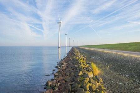 Wind turbines in a lake along a dike in sunlight at fall Stockfoto - 115446232