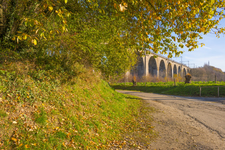 Viaduct with a railroad over a valley in sunlight at fall Stock Photo