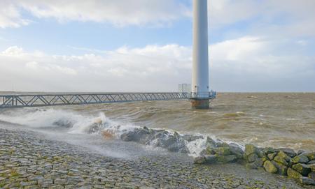 Wind farm in a stormy lake in sunlight in winter Imagens
