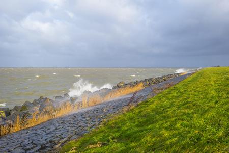 Dike along a stormy lake in sunlight in winter Stockfoto - 115445405