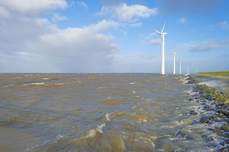 Wind farm in a stormy lake in sunlight in winter Stockfoto