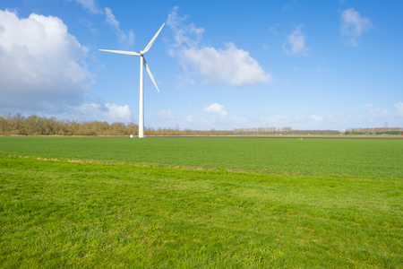 Wind turbine in a green field below a blue cloudy sky in winter Banco de Imagens