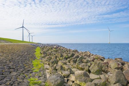 Wind farm in a lake along a dike below a blue sky in spring Stockfoto - 121675608
