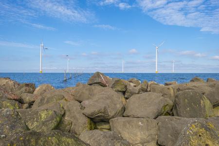Wind farm in a lake along a dike below a blue sky in spring Stock Photo