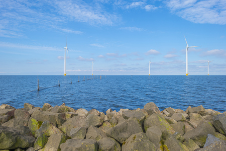 Wind farm in a lake along a dike below a blue sky in spring Stockfoto - 121675627