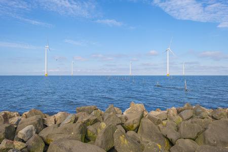 Wind farm in a lake along a dike below a blue sky in spring Stockfoto - 121675629