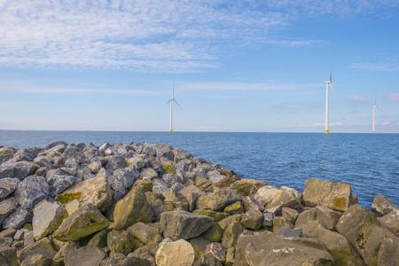 Wind farm in a lake along a dike below a blue sky in spring Stockfoto - 121675675