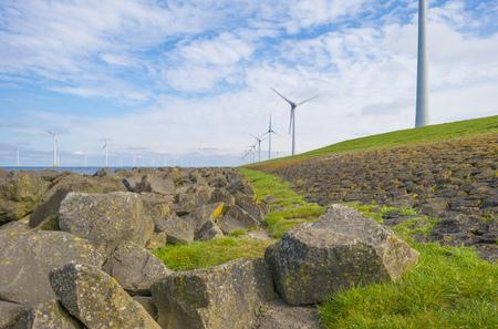 Wind farm in a lake along a dike below a blue sky in spring Stockfoto
