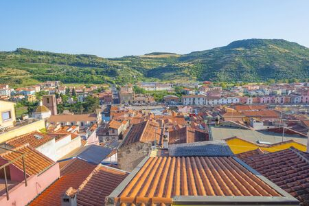 Panorama of the colorful town of Bosa along a river and hills in sunlight in spring