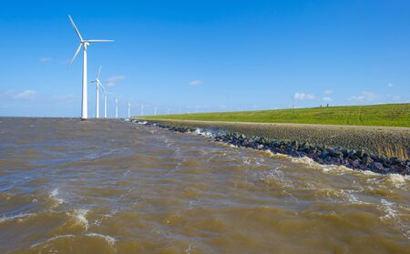 Wind farm in a lake during a storm in sunlight in winter
