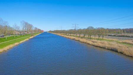 Canal separating a rural and an urban residential area below a blue sky in sunlight in spring
