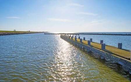 Marina along a dike and a sunlit lake below a blue sky in sunlight in spring Imagens