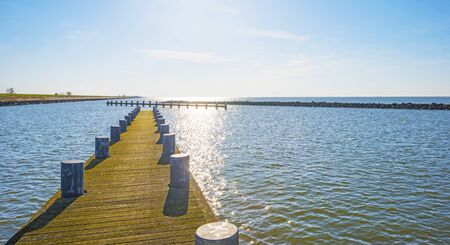 Marina along a dike and a sunlit lake below a blue sky in sunlight in spring Stockfoto