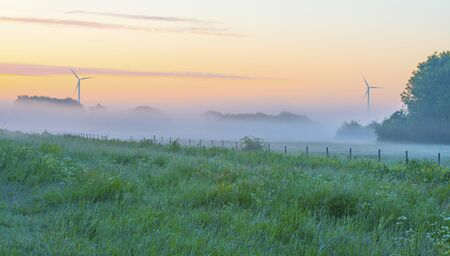 Foggy agricultural field below a misty blue yellow sky in sunlight at a misty sunrise in a spring morning