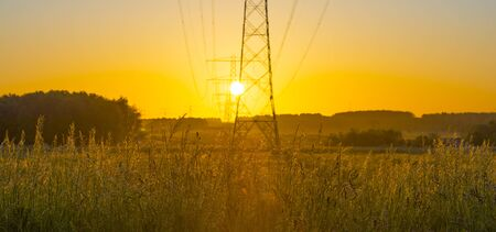 Transmission towers in grassy green field below a yellow sky in sunlight at sunrise in an early spring morning
