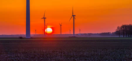 Wind turbines for renewable energy in an agricultural field in bright orange yellow sunlight at sunrise in spring, Almere, Flevoland, The Netherlands, April 17, 2021