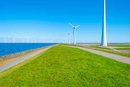 Wind turbines for renewable energy in a lake in bright blue sunlight in spring, Noordoostpolder, Flevoland, The Netherlands, April 26, 2021 Stock Photo