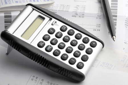 A calculator, pen, and financial statement photo