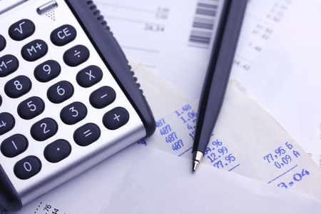 A calculator, pen, and financial statement, blue tone photo