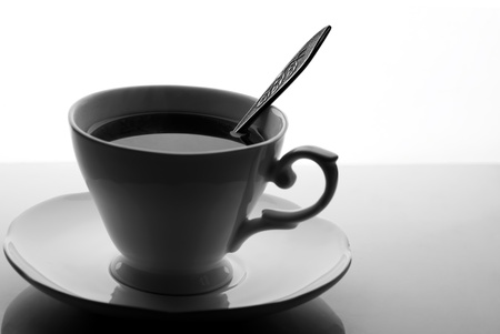 black and white picture of tea or coffee cup with spoon photo
