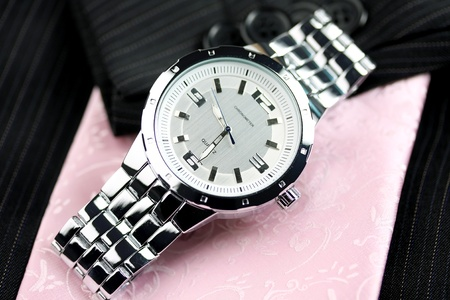 silver wristwatch over pink tie and black busiiness suit Stock Photo - 13037501