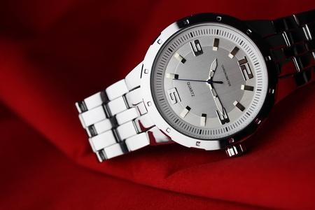 Wrist watch lying on red valvet