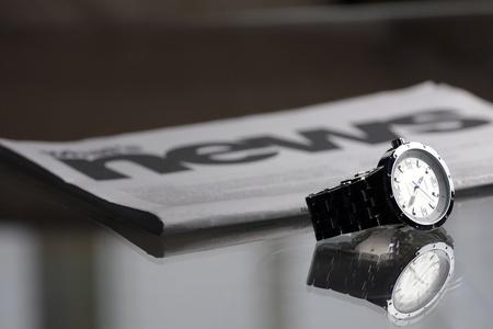 newletter: macro di orologio da polso di fronte al giornale, messa a fuoco selettiva