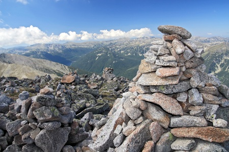 generic location: natural background of mountains, focus on stone pyramid