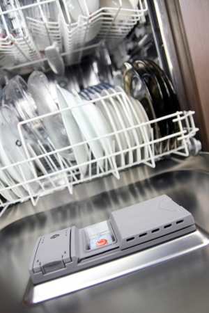 open dishwasher with clean plates in it, focus on dishwasher tabs photo