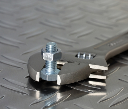 adjustable spanner, bolt and nut on diamond plate steel photo